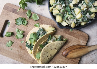 Two vegan soft tacos filled with potatoes and spinach and topped with cilantro on a cutting board with iron pan of filling on the side.