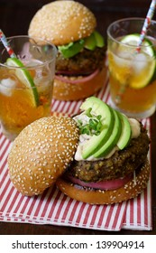 Two vegetarian sweet potato bean burgers with avocado on sesame buns, with one upper bun tilted to showcase the layers. Served with iced tea on a sheet of candy-stripe napkin