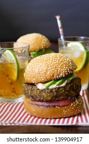 Two vegetarian sweet potato bean burgers with avocado on sesame buns, served with iced tea on a sheet of candy-stripe napkin