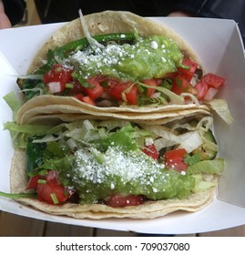Two veggie tacos filled with guacamole, tomatoes, shredded lettuce, onion, chives, topped in parmesan cheese