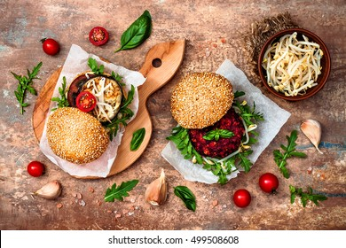 Two veggies burgers served on cutting board over stone vintage background. Vegan grilled eggplant, arugula, sprouts, pesto sauce burger. Veggie beet and quinoa burger. Top view, overhead, flat lay.