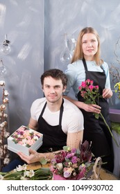 two vendors posing to camera in front of the table with flowers at shop
