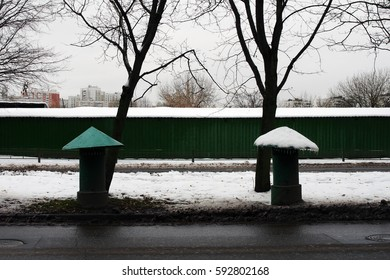 Two ventilation facilities of underground collectors. They look like mushrooms. The cap of one of them is green, the cap of another one is white because of snow. Russia, Moscow, November 2016.