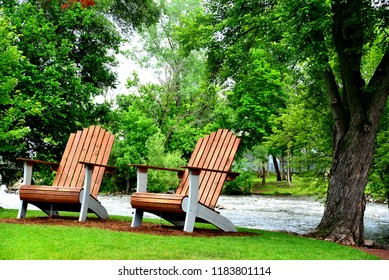 Two very large Adirondack chairs along the Fox River in Waterford Wisconsin