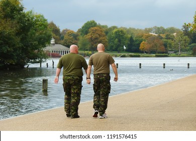 two very much alike men of sturdy build, dressed in camouflage uniforms, walking together along the pond; thunderclouds over the autumn park