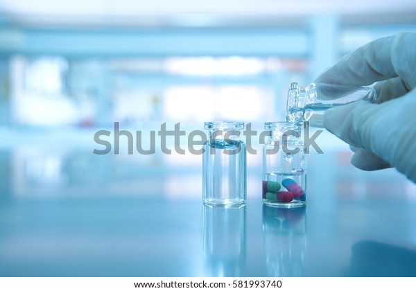 two vials with capsule pill and water and scientist pouring hand  in science laboratory