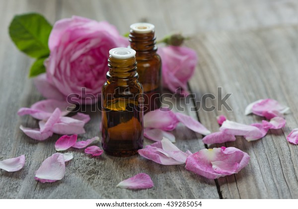 Two vials with essential oil and petals of pink roses on a wooden background