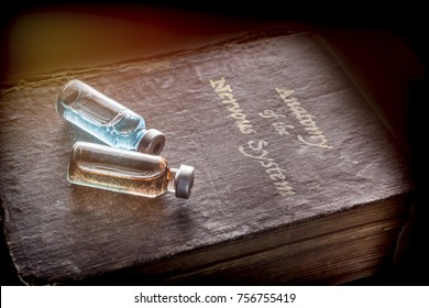 Two vials of medicine on an ancient book of Anatomy of the nervous system, conceptual image