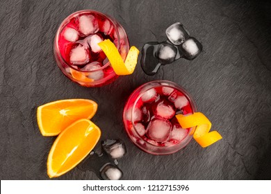 Two vibrant cocktails with campari and orange zest garnishes, shot from above, with ice cubes and fruit slices on a black background, with copy space