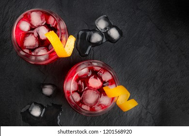 Two vibrant Negroni cocktails with campari and orange zest garnishes, shot from the top, with ice cubes on a black background, with a place for text