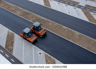 Two vibratory asphalt roller compactor on site, compacting new asphalt pavement in urban city