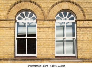 Two Victorian wooden frame white sash window with glass panels on a classic yellow brick wall with white blinders curtains
