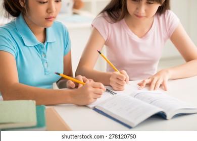 Two Vietnamese schoolgirls doing homework together