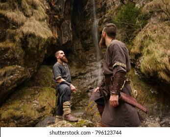Two Viking explorers posing under a big waterfall in the forest