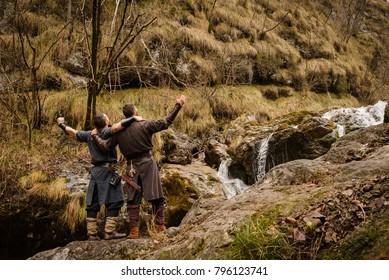 Two Viking travelers scream under the waterfall looking skyward
