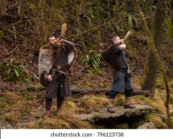 two Vikings play the horn in the forest