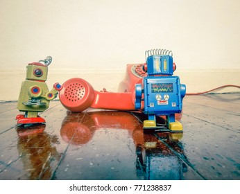 two vintabe robot with old phone on wooden floor