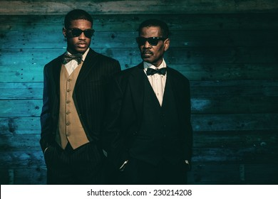 Two vintage african american gangsters in front of old wooden wall. Wearing black sunglasses and suit.