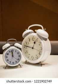 Two Vintage Alarm Clocks standing on a white desk with brown blurry sofa in background