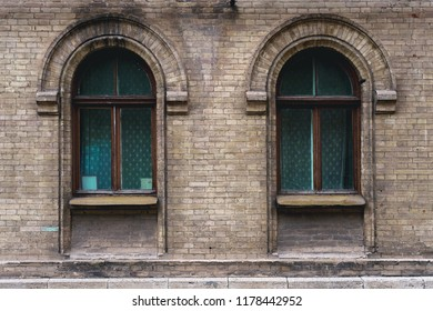Two vintage arched windows in a wall of yellow bricks. Green - the colors of sea wave glass in a maroon dark red wooden frame. The concept of antique vintage architecture in building elements
