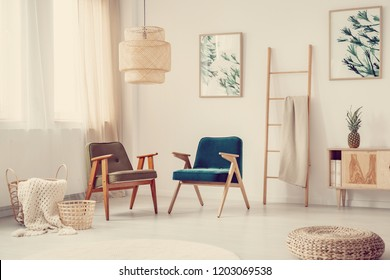 Two vintage armchairs standing in real photo of bright living room interior with window with curtains, straw baskets and wicker footrest on the floor, posters on wall and ladder with blanket