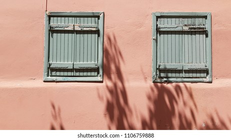 Two vintage blue windows on pink stucco wall. Old distressed window frames and cracked shutters. Minimal summer mood. Retro building in Athens Greece. Two-colored facades