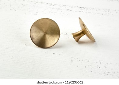 Two vintage brass drawer pull knobs on shabby white wooden background. Copy space for text.