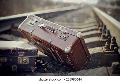 Two vintage brown suitcases are left to lie on railway rails.