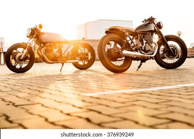 Two vintage custom motorbike caferacers motorcycle looking in opposite directions on empty rooftop parking lot with backlight sun during sunset. Confrontation of urban styles. Hipster lifestyle.