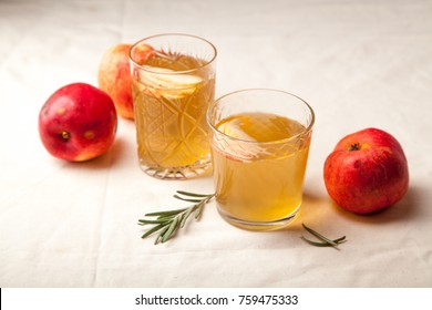 Two vintage glasses with apple cider on black background. Christmas beverages concept. Two red apples and rosemary sprig aside.  Warm backlight.