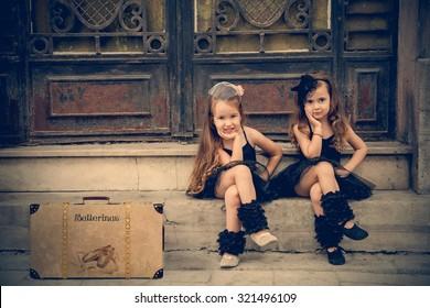 Two vintage little ballerinas in black tutu sitting on stairs