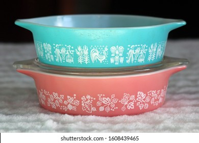 Two vintage milk-glass one-pint casserole dishes stacked on top of each other. One is aqua blue with an Amish pattern. One is pink with a gooseberry pattern.