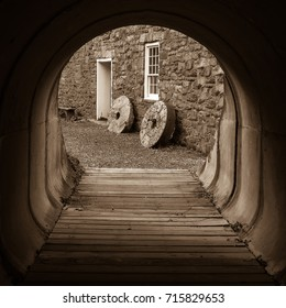 Two vintage millstones leaning on an old stone gristmill as seen from an adjacent tunnel
