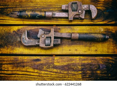Two vintage pipe wrenches on a rough wood background
