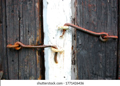 Two vintage rusty iron hasps locking old barn doors closed, traditional Scandinavian barn doors in summer closed with clasps or hasps.