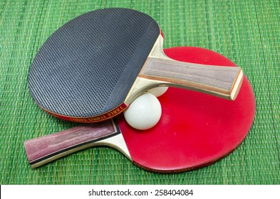 Two vintage table tennis rackets and two ping pong balls on a green background