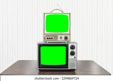 Two vintage television on old table with chroma key green screens.