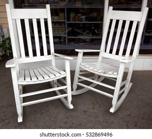 Two vintage white rocking chairs on front porch.
