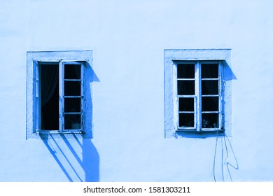 Two vintage windows on a white wall. Image is tinted in color Classic blue. Trend color 2020