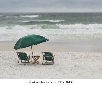 Two vintage wood and canvas lounge chairs and large umbrella overlooking stormy day at a Florida beach. Photo taken with a tilt shift lens, creative depth of field effects.