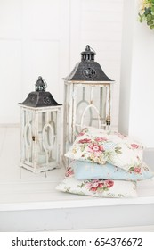 Two Vintage wooden lanterns and patterned pillows. Spring pretty background. Spring and Easter mood. Shabby chic style