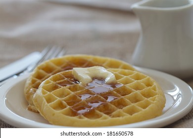 Two waffles with butter and syrup