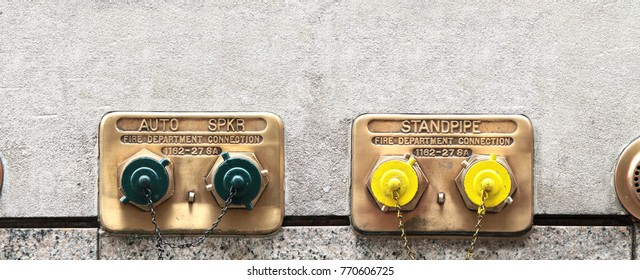 Two wall mounted brass standpipes with green and yellow caps. New York. USA.