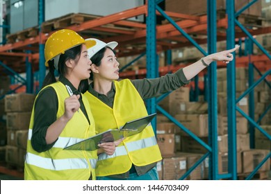 two warehouse coworkers women talking in large workplace. group of asian lady employees working in stockroom discuss place to put parcel. manager showing while point to box on shelf to colleague
