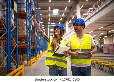 Two warehouse managers in protective work wear organizing distribution in warehouse storage area.