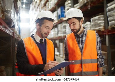 Two warehouse workers filling in document