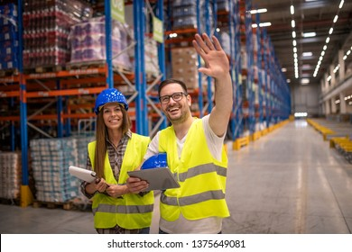 Two warehouse workers in protective work wear controlling distribution in warehouse storage area.