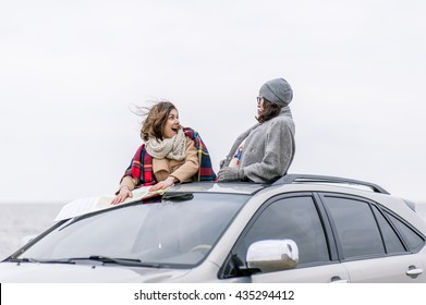Two warmly dressed European women tourists leaned out of the car roof and enjoy the life against the sea