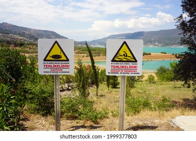 """Two Warning Signs Both in Turkish and in English by Arapapisti Canyon. """"Caution! Fishing in this area is dangerous!"""" and """"Danger of drowning! No swimming, no boating, no wading"""""""