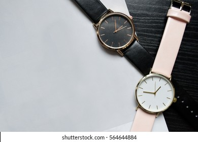 Two watches black and pink color, without numbers on a black table. Light paper, place for your text. Fashionable concept, top view